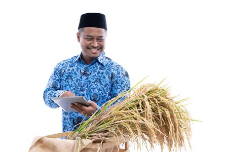 asian man with batik checked quality of rice grain 스톡 콘텐츠