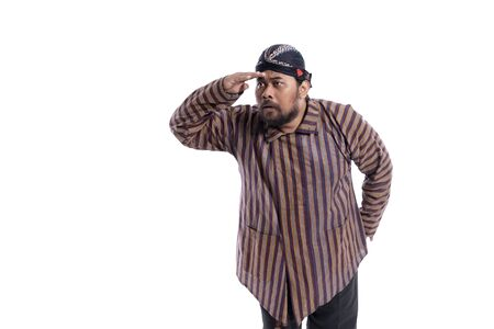 man with javanese traditional cloth lurik looking up for something Stock Photo
