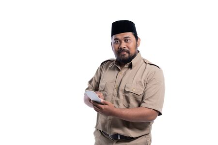 worker with brown uniform indonesia smiling using phone Stock Photo