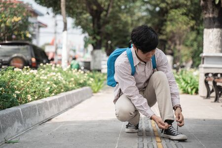 college man student fixing shoelaces while walking to campus