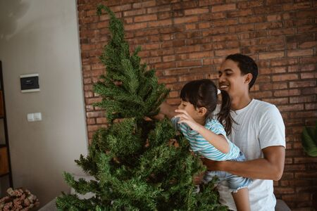 asian father with daughter set up christmas tree together