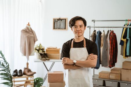 proud young online ecommerce shop owner standing at his office
