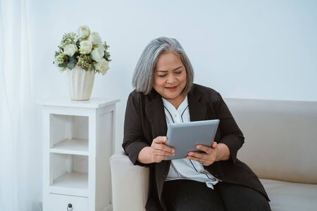 Confident old woman is very beautiful when handling an online business 写真素材