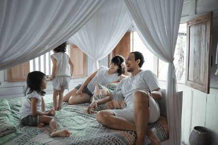 Asian happy family and child daughter relaxing on the bed Stockfoto - 134310127