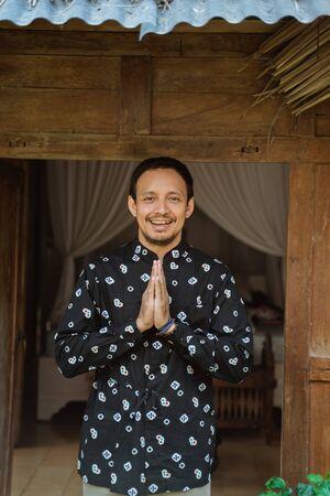 从传统房子的亚洲年轻男性欢迎问候