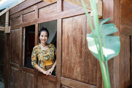 beautiful asian woman wearing a kebaya smiling when leaning against the window