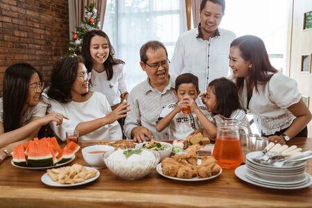 familia animando durante el almuerzo juntos en casa Foto de archivo