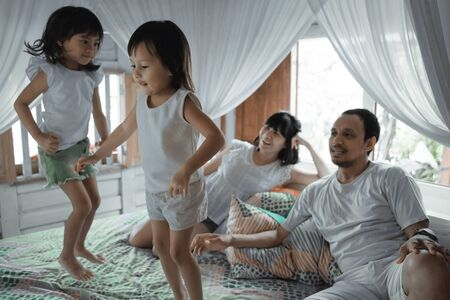 Happy family playing together on the bed Stockfoto - 134234570