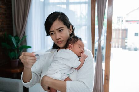 asian mother using thermometer feel worried about their childrens health