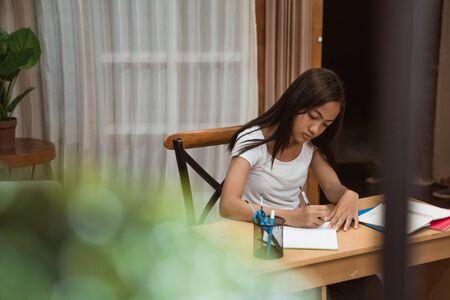 asian teenager doing homework at home