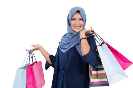 Asian older veiled woman happy carrying a lot of shopping bags