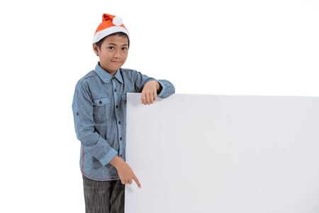 kid with santa claus hat smiling holding blank board Stock Photo