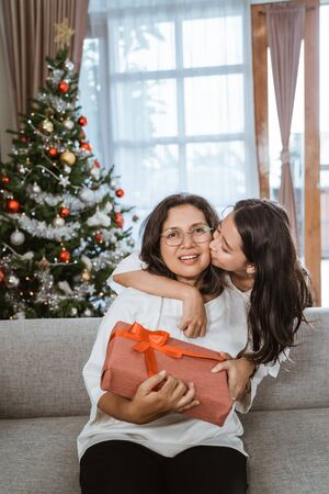 daughter kiss mother on cheek during christmas