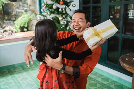 daughter giving her father a present on christmas day