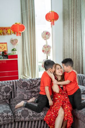 Smiling chinese mother and two son wearing red theme,one of his son kissing his mother