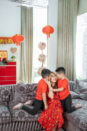 Smiling asian chinese mother and two son wearing red theme clothing,one of his son kissing his mother Banco de Imagens