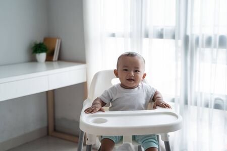 asian baby boy sitting on high chair Stock Photo