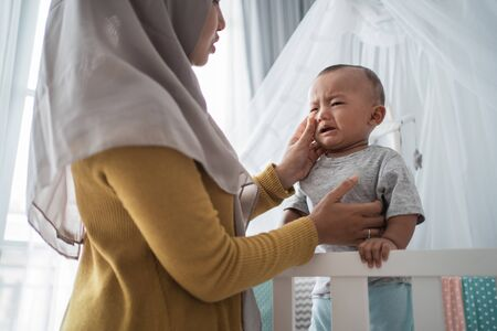 Mother try to comfort her cry child at the crib Banque d'images - 138378480