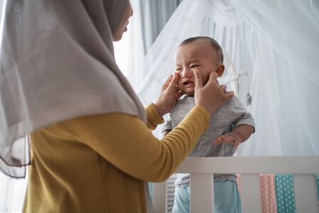 Mother try to comfort her cry child at the crib