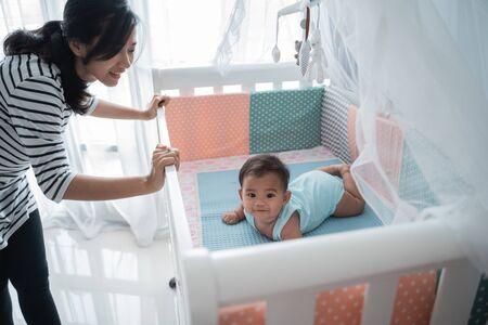 asiatisches glückliches Baby auf der Krippe Standard-Bild