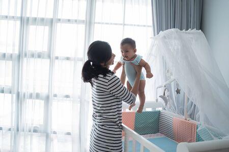 Asian happy baby on the crib Banco de Imagens