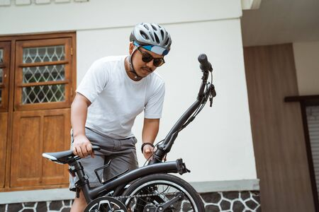 Asian mens sunglasses try folding his folding bike to get ready to go to work