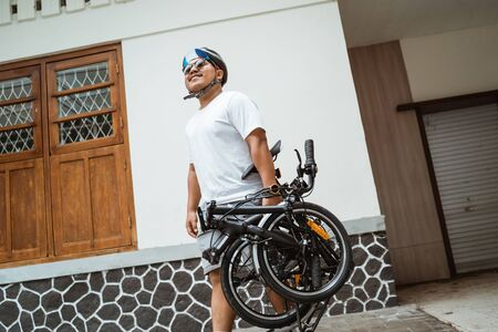 asian young man walking and carrying her folding bike