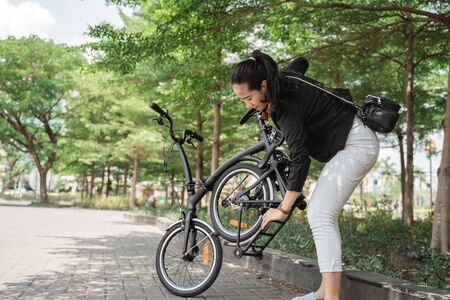 preparing worker woman trying fold her folding bike when go to office