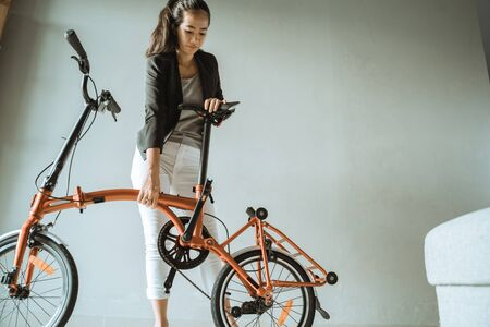 asian young woman stand on living room when open fold her folding bike