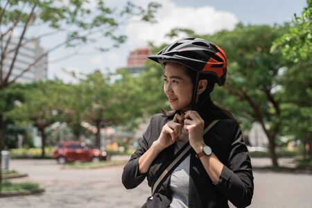 asian young woman wearing helmet bike for safety