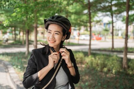 smiling woman wearing helmet for safety when go by bike to work Stockfoto