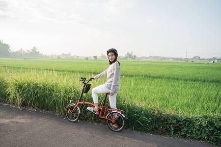 young women wear helmets to ride folding bikes in rice fields background Banco de Imagens - 138465739