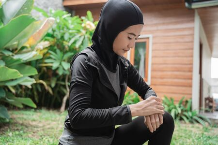 hijab sporty Asian woman looking at a smart wristband to set the time