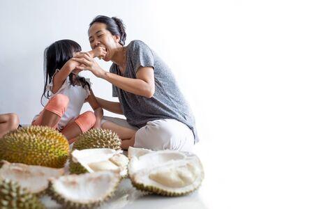 kid feeding her mother durian fruit