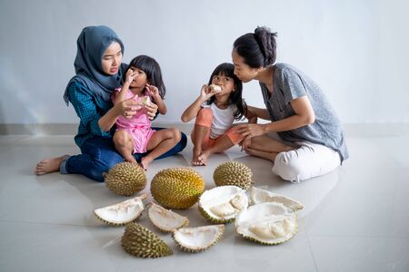 woman with kids eating durian fruit Stock Photo