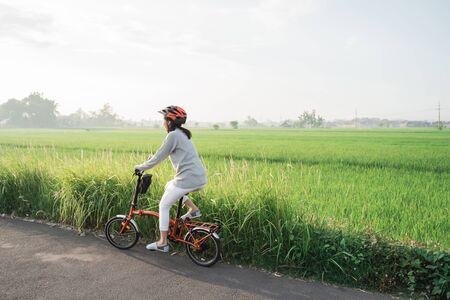 Asian women wear helmets to ride folding bikes in the rice fields in the morning Banco de Imagens - 138382330