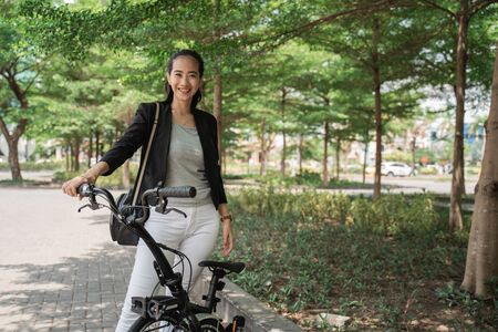 Woman asian young worker standing with her folding bike