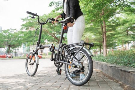 asian woman worker holding her folding bike when go to office Stockfoto