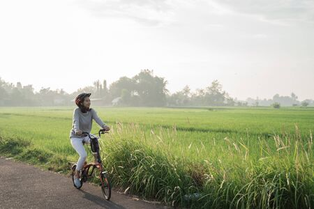 Asian women wear helmets to ride folding bikes in the rice fields in the morning