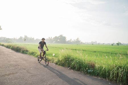 young male wear helmets to ride folding bikes for sports in rice fields background