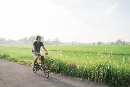 Asian young male wear helmets to ride folding bikes in the rice fields in the morning