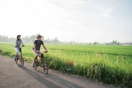 young couple wear helmets to ride folding bikes for sports in rice fields background