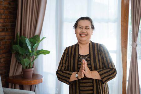 Lächeln Sie asiatische alte Frau Frau stehend mit Batik Lurik