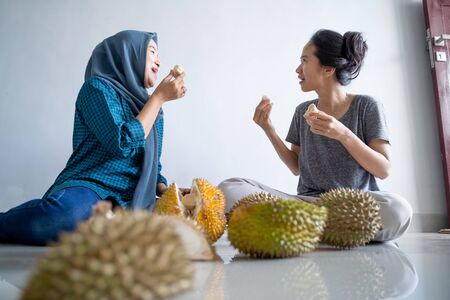 muslim friend eating durian fruit Stock Photo