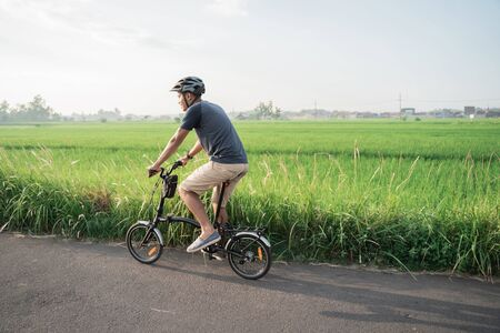 Asian young male wear helmets to ride folding bikes in the rice fields