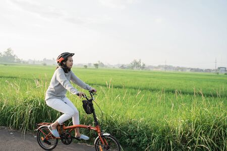 young women wear helmets to ride folding bikes in rice fields background Banco de Imagens - 138469274