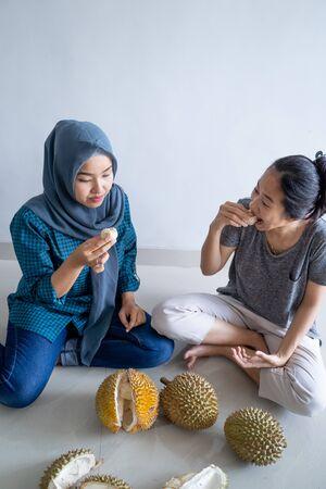 muslim friend eating durian fruit Stock Photo