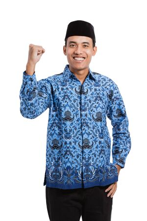 asian young man wearing batik korpri with spirited hand gesture 免版税图像