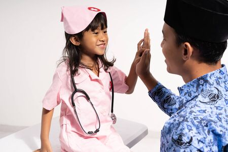 asian father wearing batik korpri with high five hands by her daughter wearing doctor uniform
