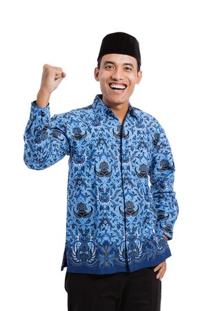 smiling asian young man wearing batik korpri with spirited hand gesture